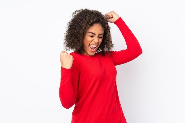 Jonge vrouw die op muur wordt geïsoleerd die een overwinning viert