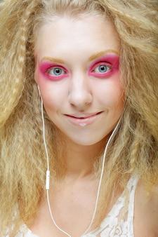 Jonge vrouw die op muziek op haar hoofdtelefoons danst