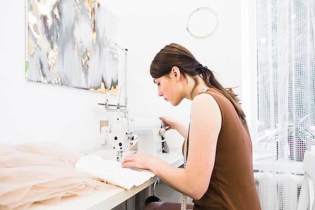 Jonge vrouw die op naaimachine naaien