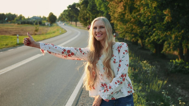 Jonge vrouw die op plattelandsweg liften