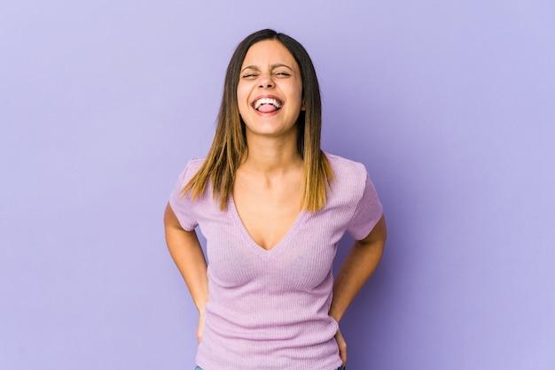 Jonge vrouw die op purpere grappige en vriendschappelijke uitstekende tong wordt geïsoleerd.