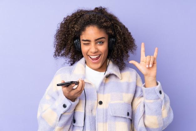 Jonge vrouw die op purpere muur het luisteren muziek wordt geïsoleerd met een mobiel het maken rotsgebaar
