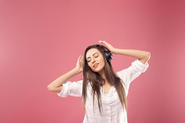 Jonge vrouw die op roze achtergrond aan muziek met draadloze hoofdtelefoons luistert