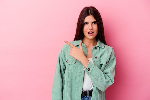 Jonge vrouw die op roze muur wordt geïsoleerd die naar de kant richt