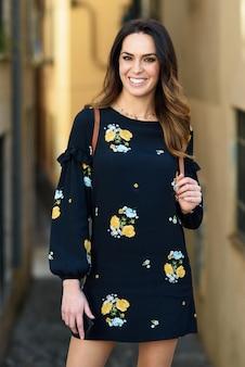Jonge vrouw die op stedelijke achtergrond loopt. vrouw in vrijetijdskleding met zorghaar.