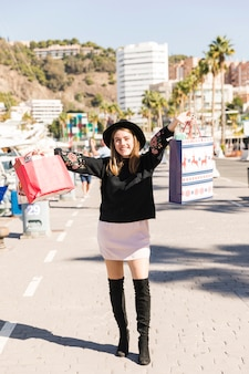 Jonge vrouw die op straat met het winkelen zakken loopt