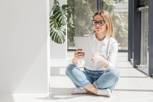 Jonge vrouw die op tablet kijkt