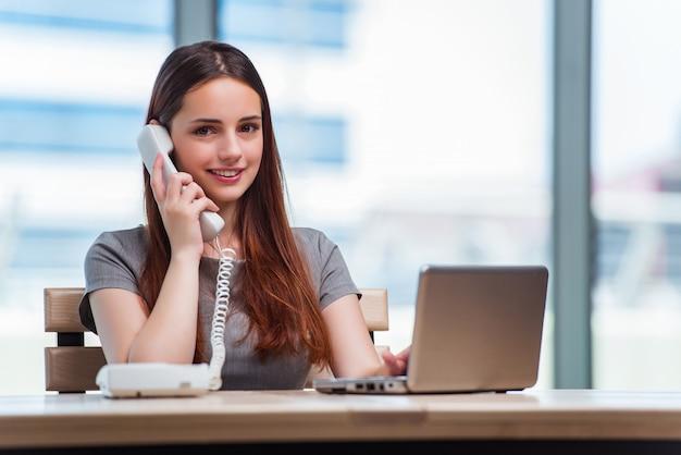 Jonge vrouw die op telefoon in bureau spreekt