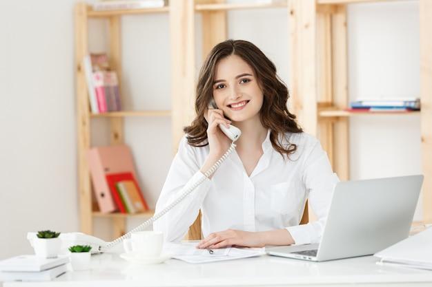Jonge vrouw die op telefoon in modern bureau spreekt.