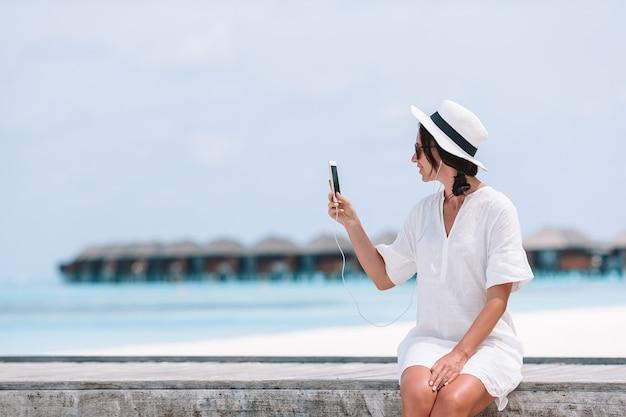 Jonge vrouw die op telefoon tijdens tropische strandvakantie spreekt