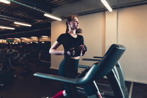 Jonge vrouw die op tredmolen bij gymnastiek loopt