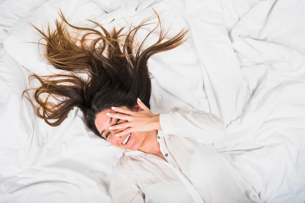 Jonge vrouw die op verfrommeld bed ligt dat door vinger gluurt