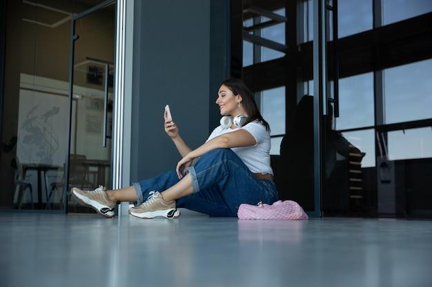 Jonge vrouw die op vertrek op de luchthaven wacht, reiziger met kleine bagage, influencer