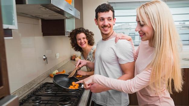 Jonge vrouw die op voedsel richt dat door haar mannelijke vriend wordt voorbereid