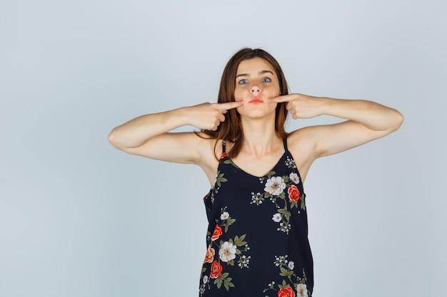 Jonge vrouw die op wangen drukt met vingers in blouse en verbaasd kijkt. vooraanzicht.