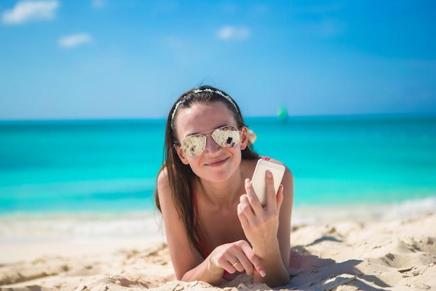 Jonge vrouw die op wit zand ligt en door haar telefoon spreekt
