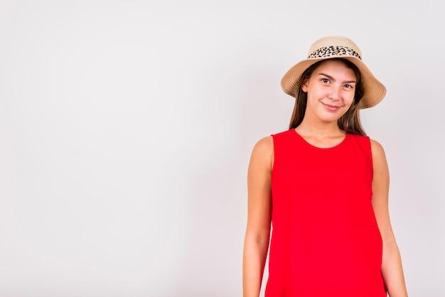 Jonge vrouw die op witte achtergrond glimlacht