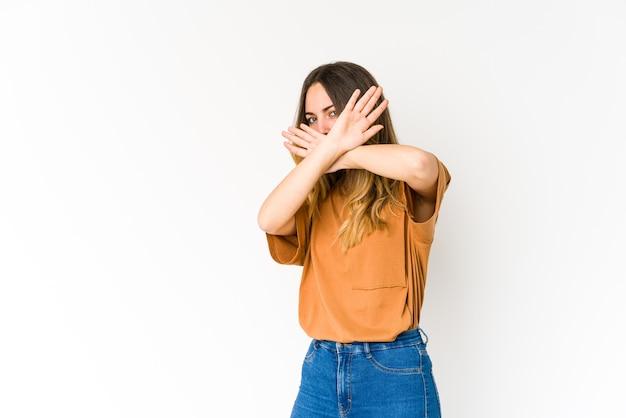 Jonge vrouw die op witte muur wordt geïsoleerd die twee gekruiste wapens houdt, ontkenningsconcept