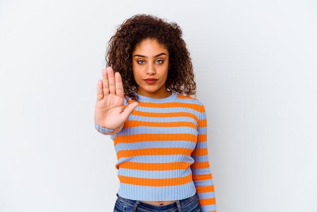 Jonge vrouw die op witte muur wordt geïsoleerd die zich met uitgestrekte hand bevindt die eindeteken toont, dat u verhindert