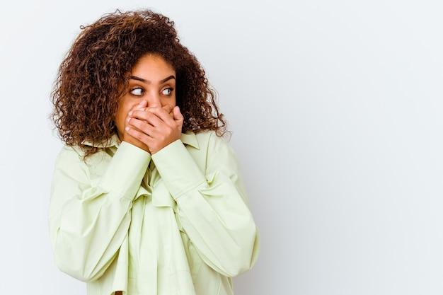 Jonge vrouw die op witte muur wordt geïsoleerd het nadenkende op zoek naar een exemplaarruimte die mond behandelt met hand