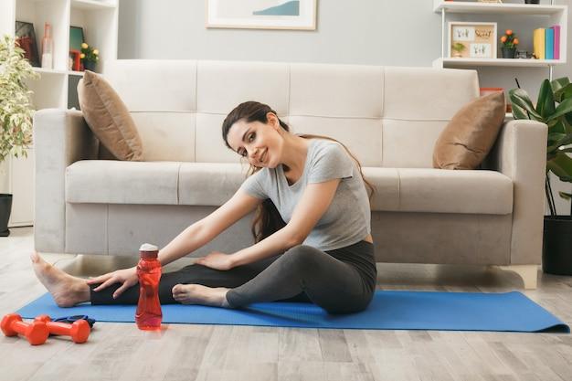 Jonge vrouw die op yogamat voor bank in woonkamer uitoefent