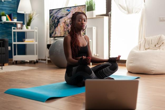 Jonge vrouw die op yogamat zit en kalme harmonie beoefent en zen mediteert voor een gezonde levensstijl, ontspannen in lotushouding