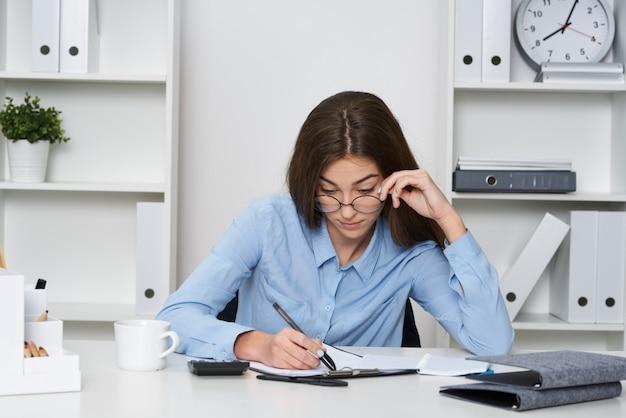 Jonge vrouw die op zeer bezig kantoor werkt