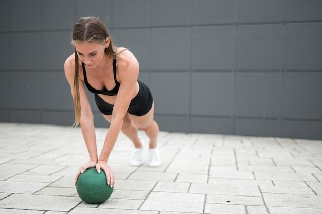 Jonge vrouw die opdrukoefeningen doet lang schot