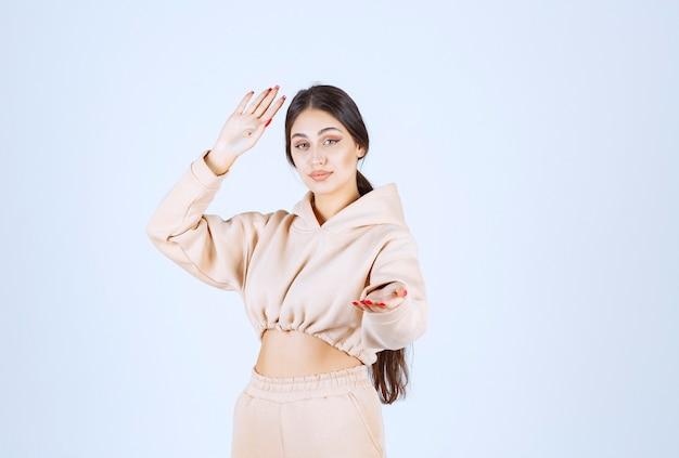 Jonge vrouw die open handen gebruikt om over iets te presenteren en te praten