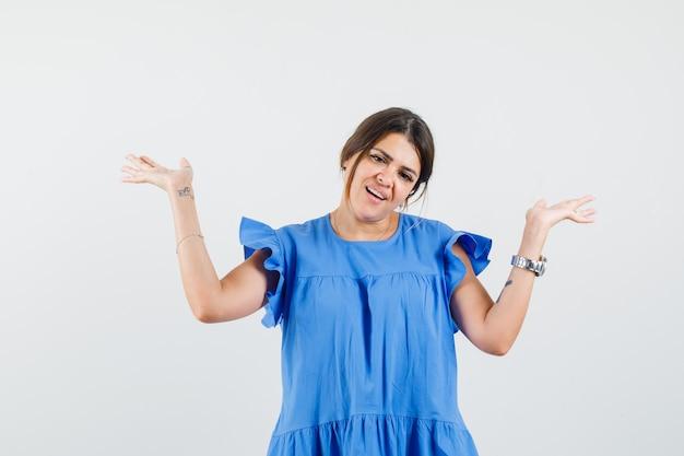 Jonge vrouw die open handpalmen in blauwe kleding opheft en speels kijkt