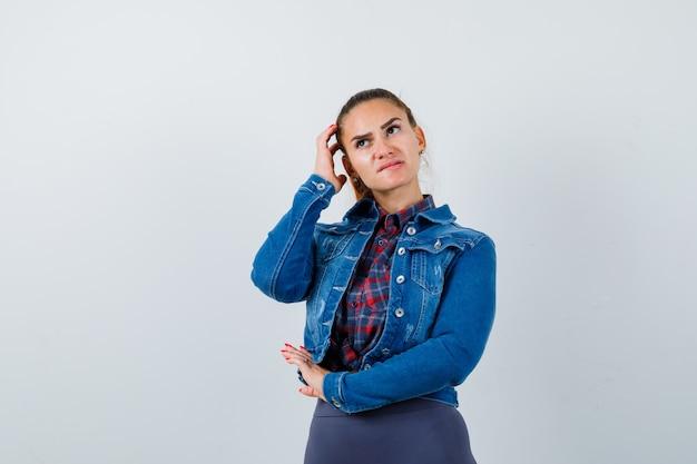 Jonge vrouw die opkijkt terwijl ze haar hoofd krabt in een geruit hemd, jas, broek en er attent uitziet. vooraanzicht.