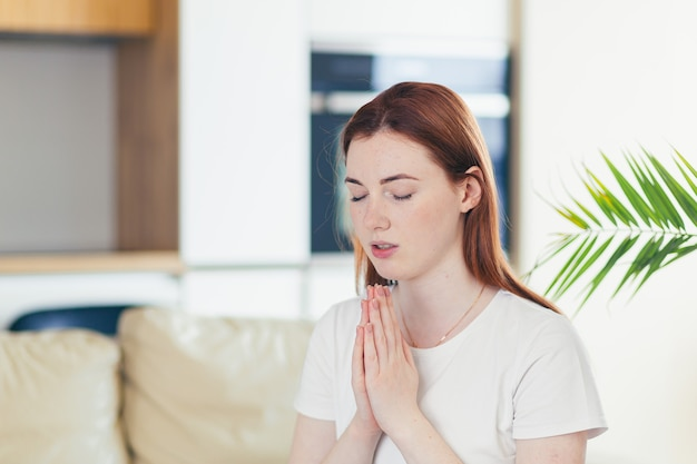 Jonge vrouw die oprecht bidt met gevouwen armen thuis