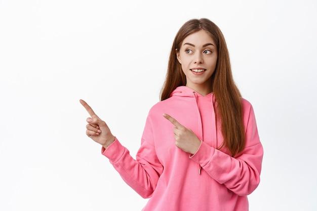 Jonge vrouw die opzij wijst, naar de linker kopieerruimte kijkt met een nieuwsgierige uitdrukking, promo bekijkt, tegen een witte muur staat