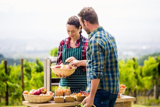 Jonge vrouw die organische groenten verkoopt aan de mens bij landbouwbedrijf
