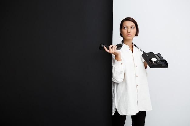 Jonge vrouw die oude telefoon over zwart-witte oppervlakte houdt