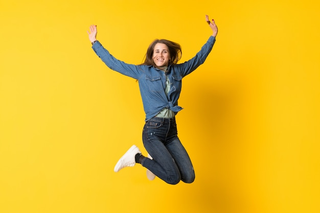Jonge vrouw die over geel springt