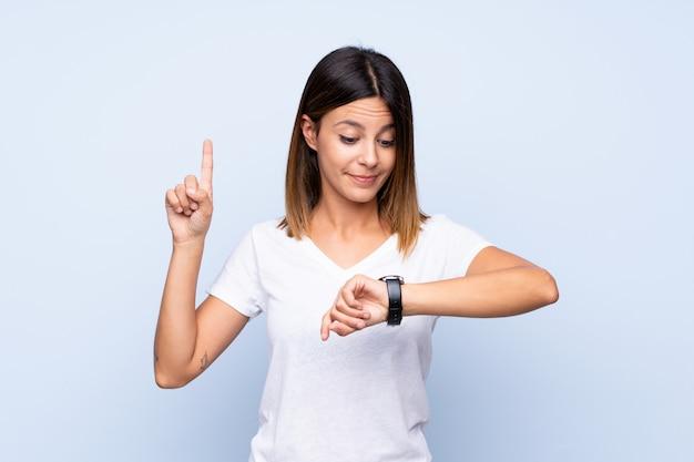 Jonge vrouw die over geïsoleerd blauw het handhorloge bekijkt
