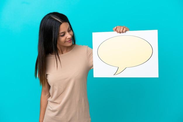 Jonge vrouw die over geïsoleerde achtergrond een plakkaat met het pictogram van de toespraakbel houdt