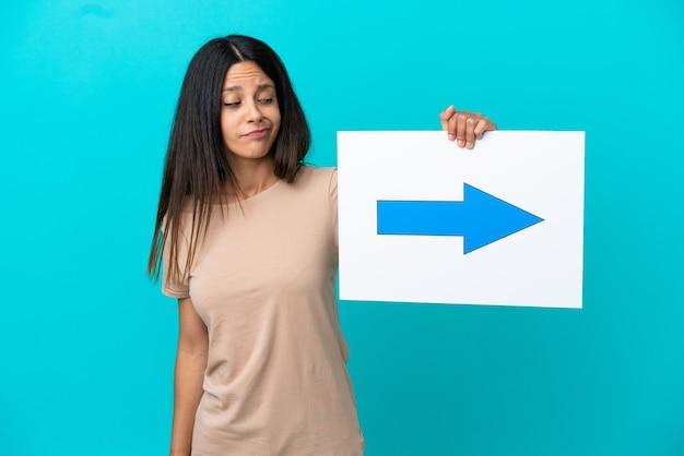 Jonge vrouw die over geïsoleerde achtergrond een plakkaat met pijlsymbool houdt