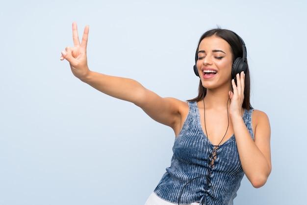 Jonge vrouw die over geïsoleerde blauwe muur aan muziek met hoofdtelefoons luistert