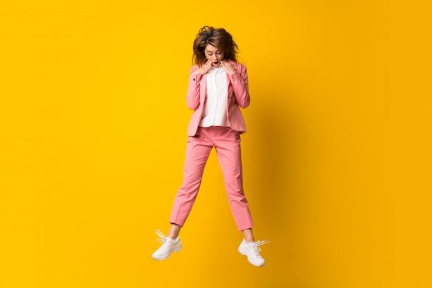 Jonge vrouw die over geïsoleerde gele muur springend verrassingsgebaar springen