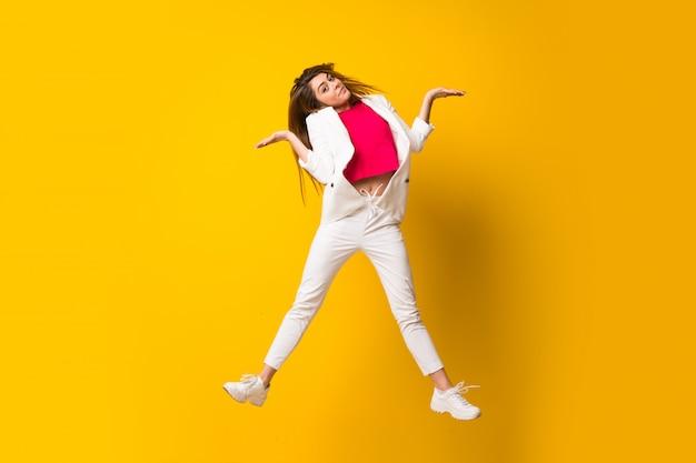 Jonge vrouw die over geïsoleerde gele muur springt die twijfels heeft