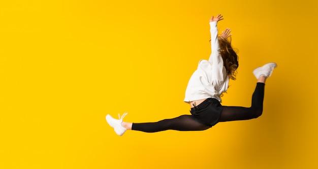 Jonge vrouw die over geïsoleerde gele muur springt