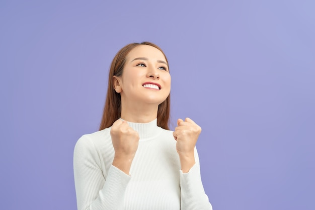 Jonge vrouw die over geïsoleerde violette muur een overwinning viert