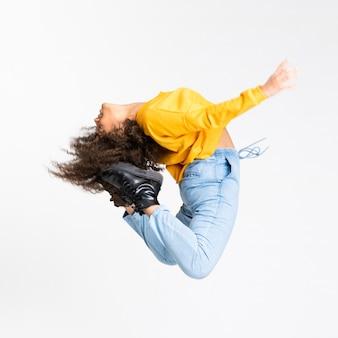 Jonge vrouw die over geïsoleerde witte muur danst