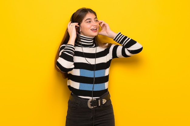 Jonge vrouw die over gele muur aan muziek met hoofdtelefoons luistert