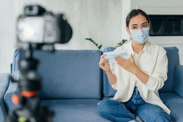 Jonge vrouw die over gezichtsmaskers vlogt
