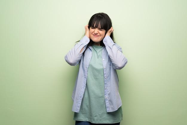 Jonge vrouw die over groene muur oren behandelt met handen. gefrustreerde uitdrukking