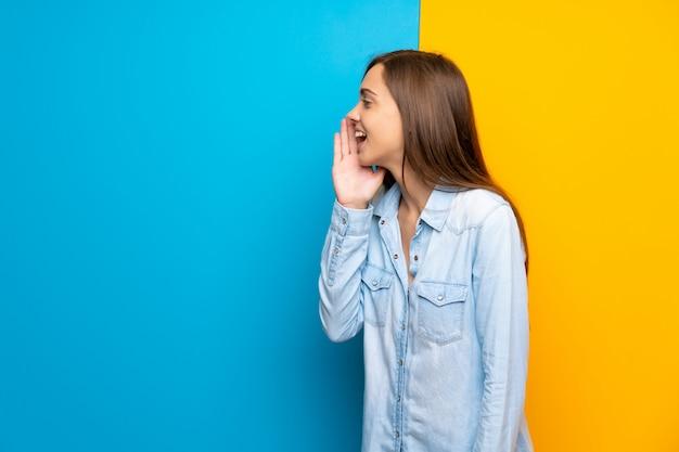 Jonge vrouw die over kleurrijke achtergrond met wijd open mond schreeuwen