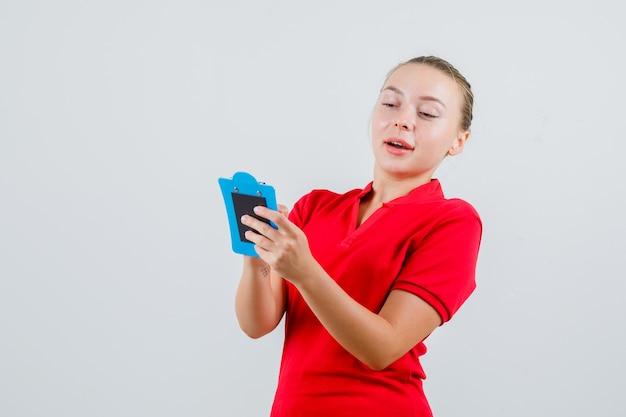 Jonge vrouw die over nota's op klembord in rood t-shirt kijkt en positief kijkt